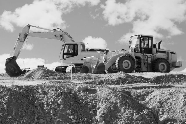 Black and white photo of a bull dozer and backhoe