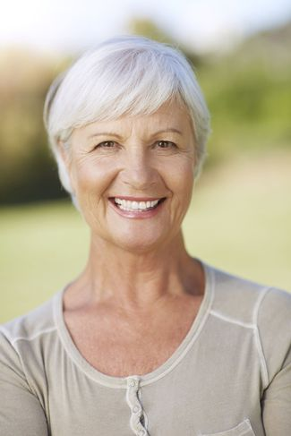 Smiling woman with gray hair and beige top