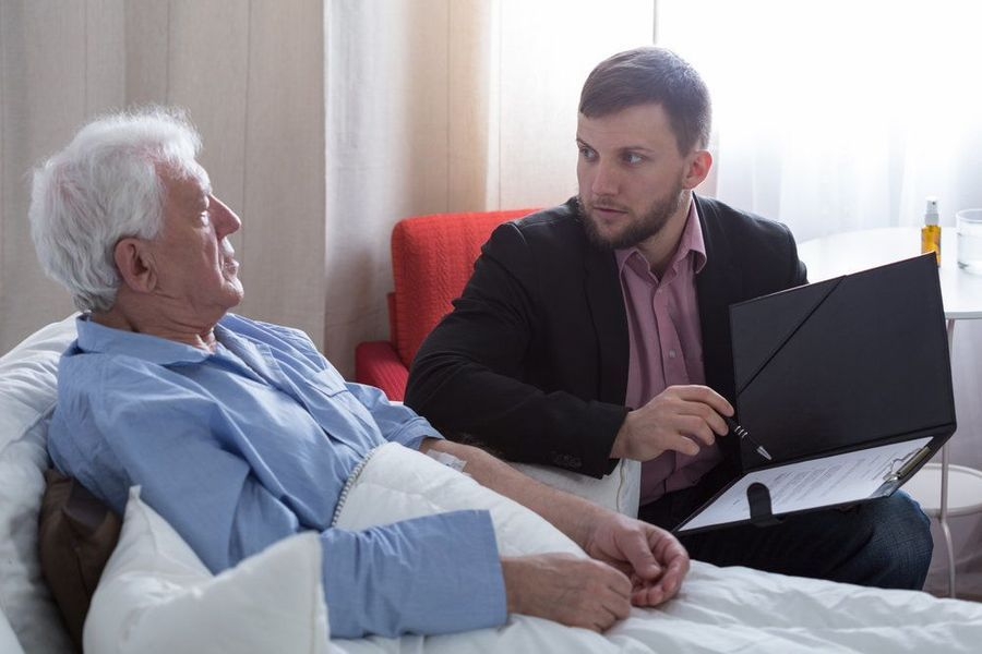 Man in suit with paperwork talking to elderly man in bed