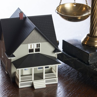 Photo of a miniature house next to legal scales