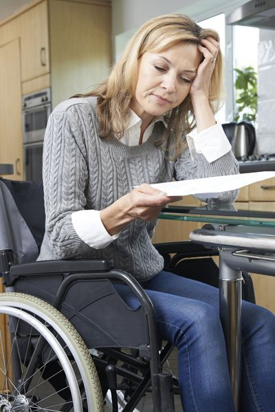 Woman in wheelchair holding head in hands and looking at paperwork