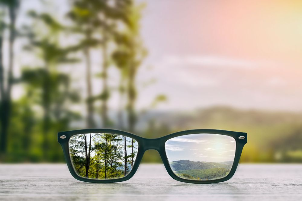 A blurred horizon is shown clearly through a pair of glasses sitting on a table.