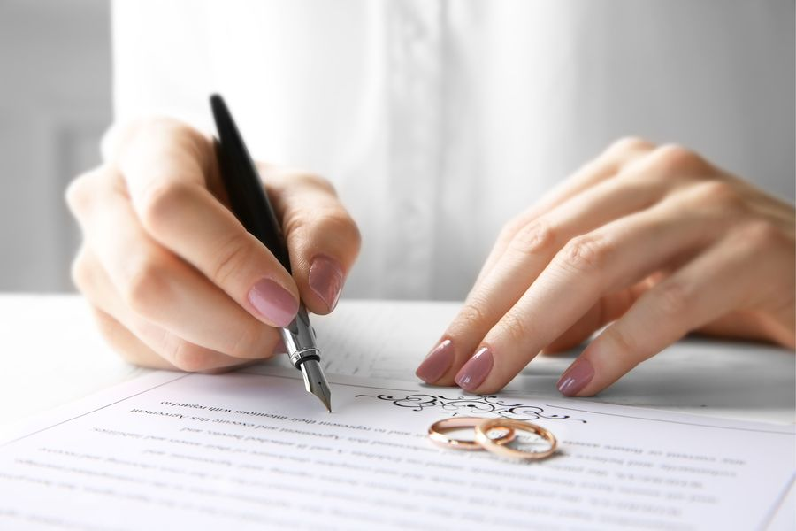 Wedding rings next to woman's hands signing legal paperwork