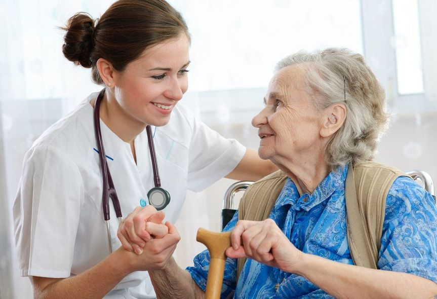 A young nurse wearing a stethoscope holds the hand of an elderly patient.