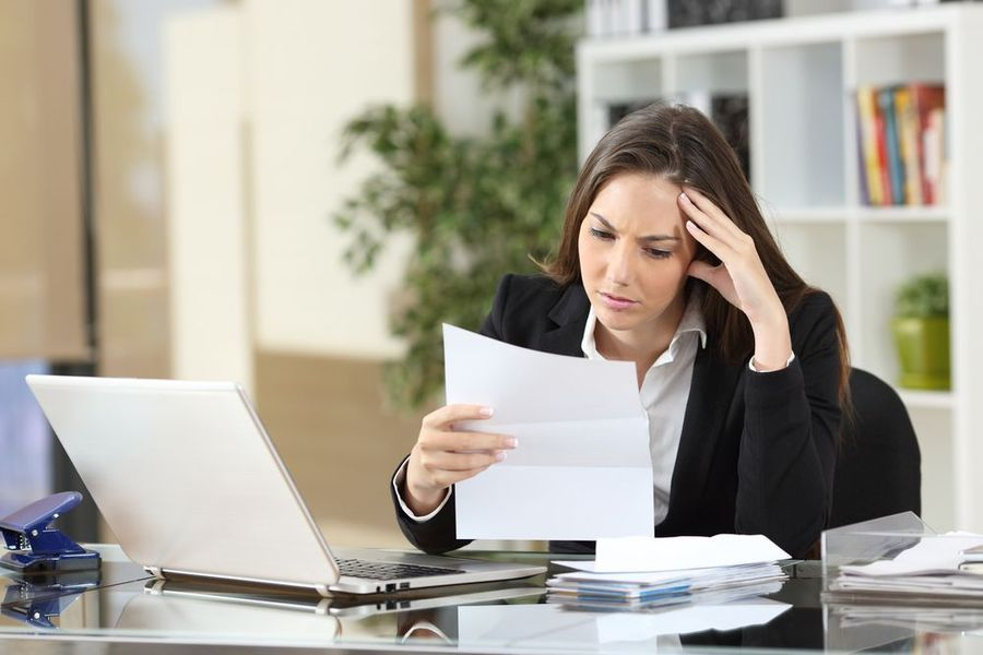Upset woman in business suit looking at paperwork