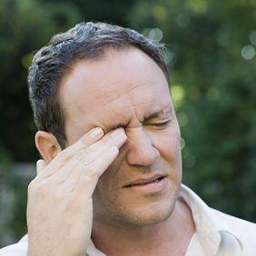 Man rubbing eye in irritation