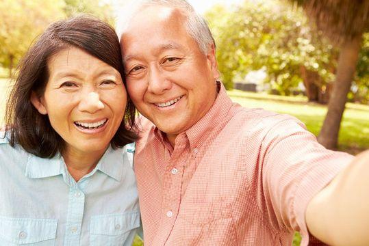 Smiling couple taking taking selfie in park