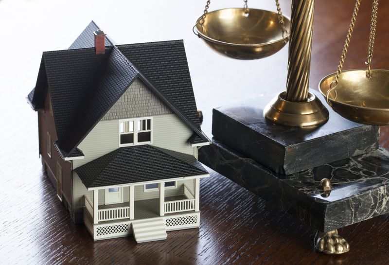 Photo of a miniature house next to a set of legal scales
