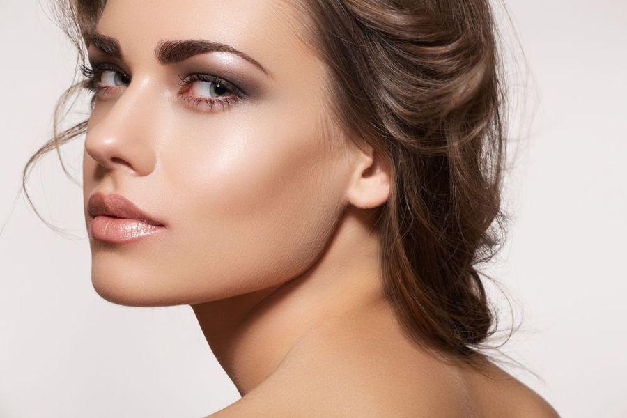 Una bella y joven mujer con el pelo recogido en una morenita mira seductoramente sobre su hombro.