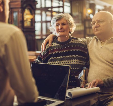 Elderly couple speaking to man on laptop