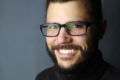 A smiling, bearded man with glasses