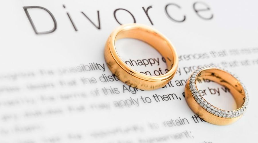 Two wedding rings rest on a dictionary definition of divorce