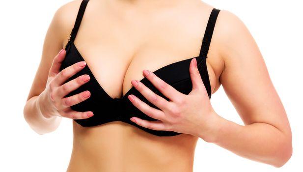 caucasian woman holding breasts in black bra breast lift benefits