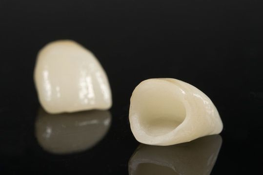 A dental crown lying on its side next to an upright dental crown.