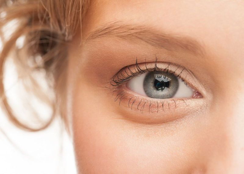 A closeup view of a woman's grayish-blue eye.