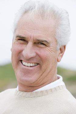 A grey-haired man smiling outdoors
