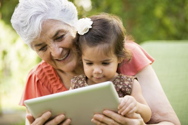 Photo of older woman holding child and looking at a tablet