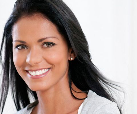 Dark-haired woman smiling against a white background