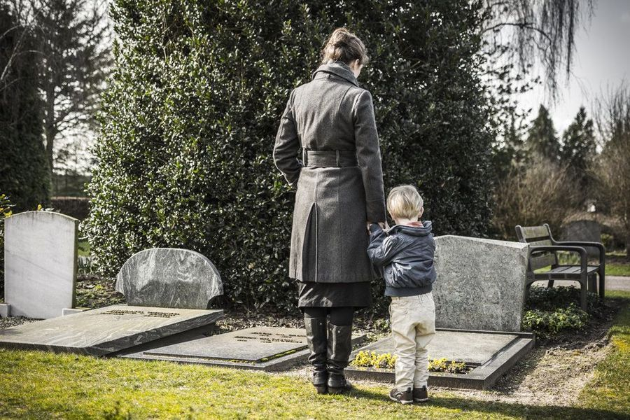 Woman and small son standing at gravestone