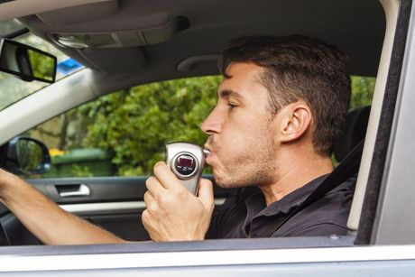 A man blowing into an ignition interlock device