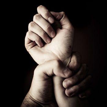 Man's hand grasping woman's wrist