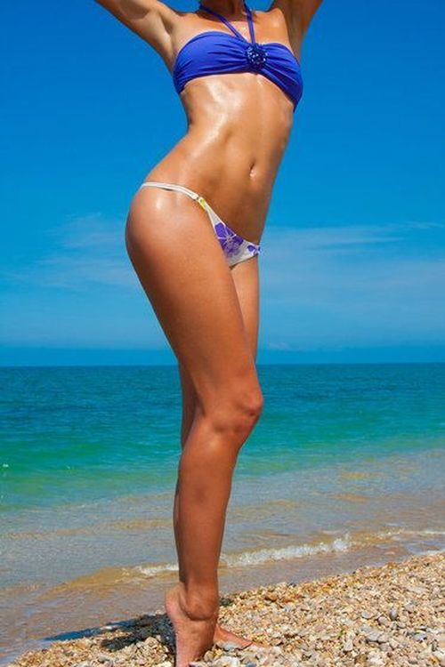 Woman's slim legs and torso on beach