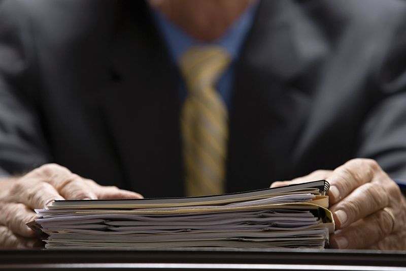Photo of hands holding a binder of papers