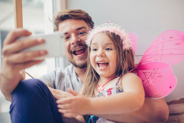 A man and a young girl smile and take a selfie