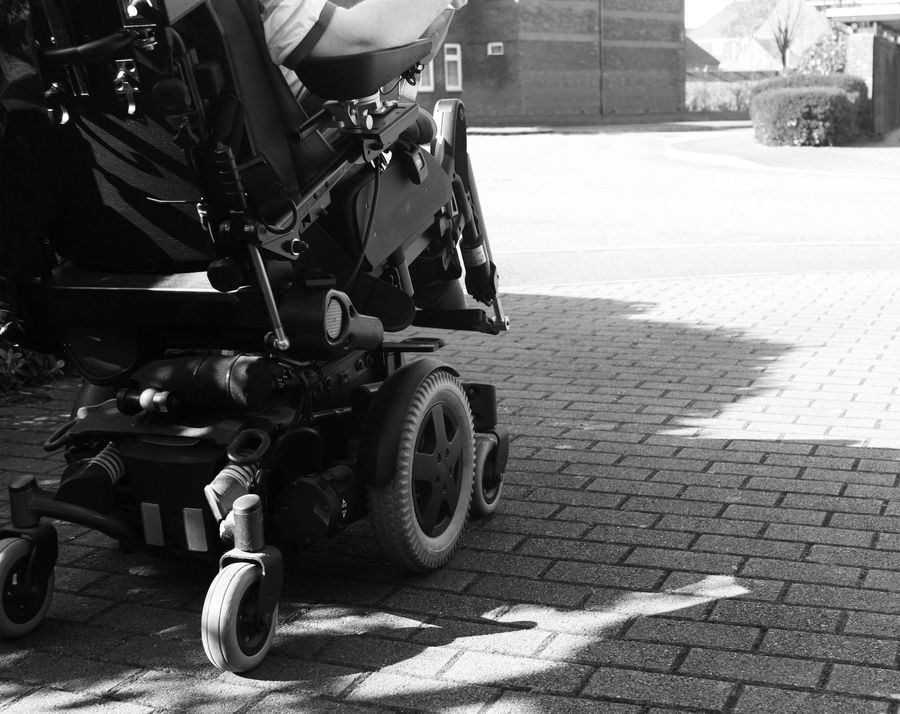 Wheelchair from behind on sidewalk