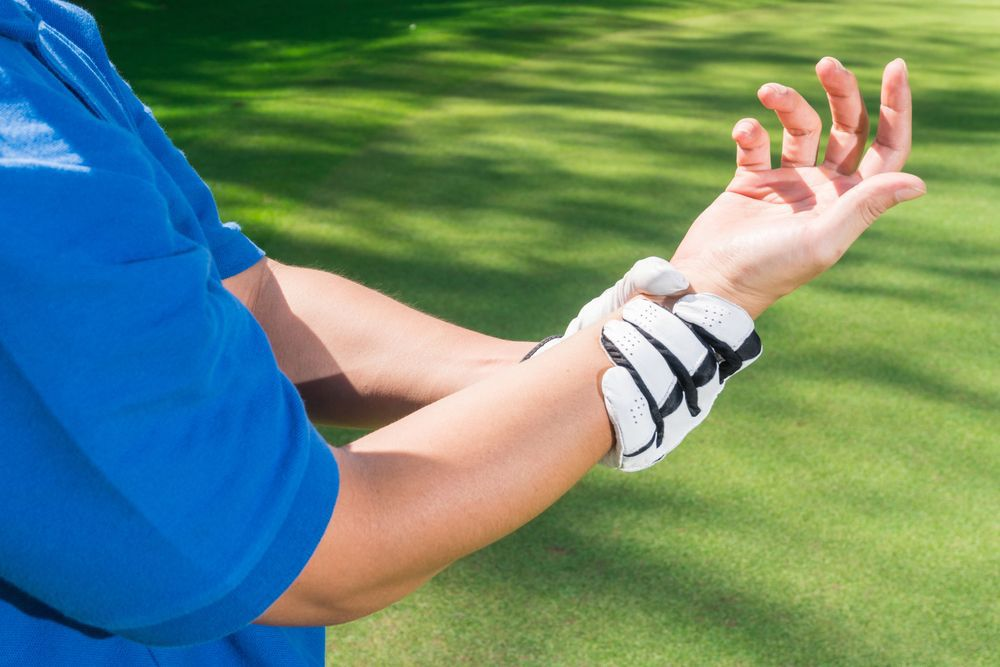 A golfer grips her wrist in pain