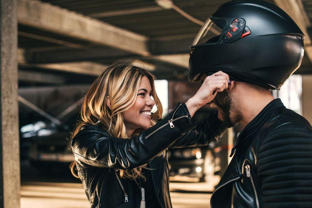 Smiling woman pulling helmet over man'd head