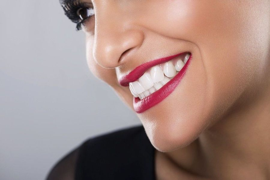 Close up of woman's bright white teeth and berry lipstick