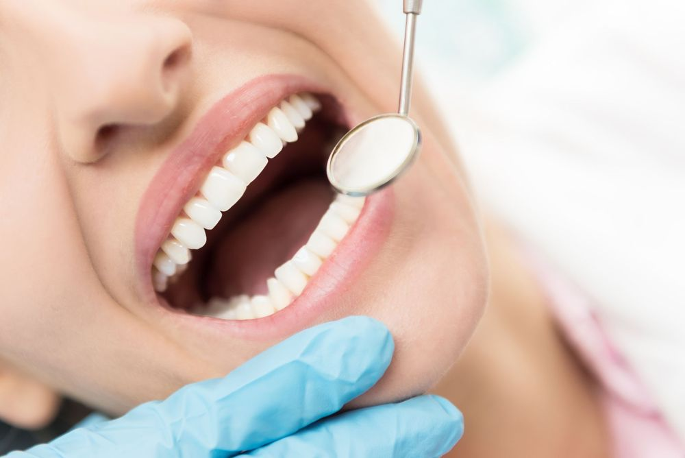 Dental exam mirror next to woman's teeth