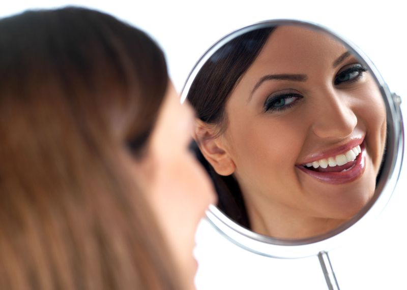 Woman smiling into handheld mirror