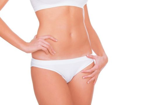 Slim female abdomen in white underwear