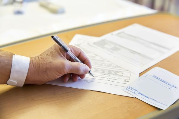 Close-up of a hand signing legal documents