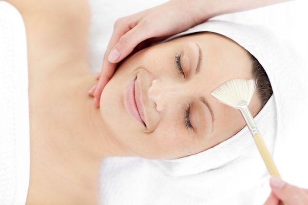 Smiling woman receiving skin treatment