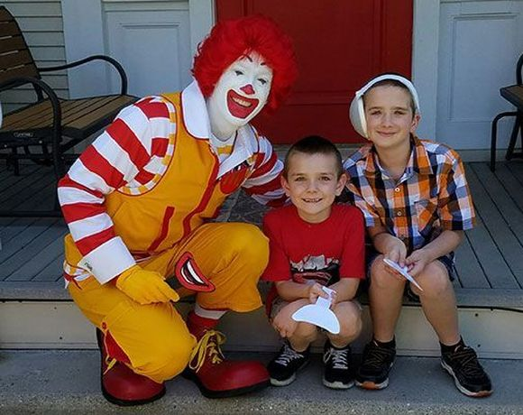Ronald McDonald posing with two kids after ear surgery