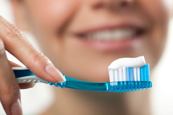 Blurred woman smiling with toothbrush and toothpaste in foreground