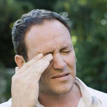 Man rubbing eye in irritation