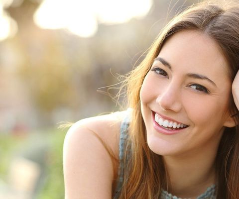 Young brunette woman smiling outdoors