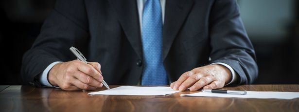 Man in business suit signing paperwork
