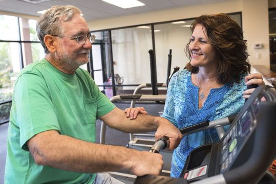 Grey-haired man on a treadmill with a supportive woman nearby
