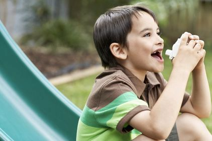 Boy on a slide with his inhaler