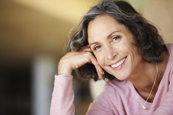 Smiling woman with hand on her head.