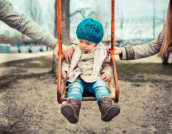 Image of child being pushed in swing by mother and father