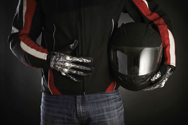 Photo of a person holding a motorcycle helmet