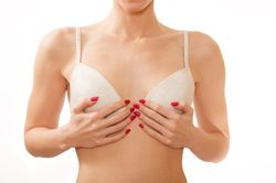 Woman covering her breasts, posing in a bra.