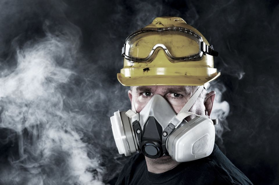 Photo of man with respirator on in a smoky room