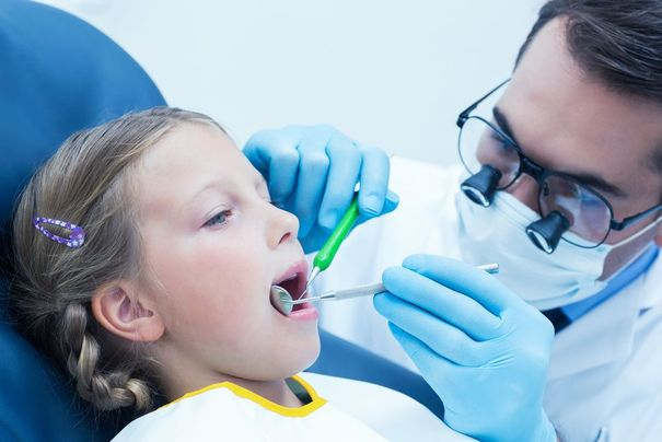 Dentist with loupes examining girl's teeth